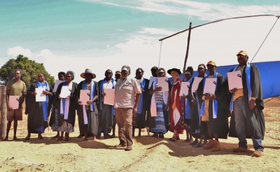 Leader of Madarrpa Clan, Djambawa Marawili, AM, (center) stands with graduates and Menzies' Dr Alice Mitchell at Yilpara homeland graduation ceremony